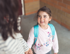 Child smiling and holding hands