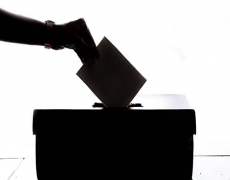 Person dropping voting paper in box